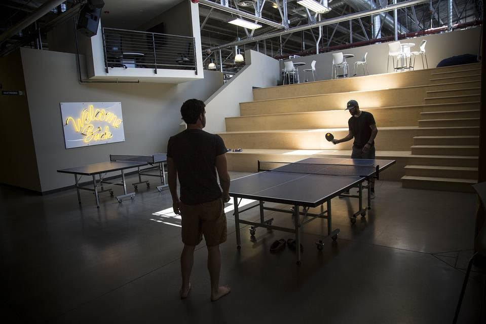 Employees at Industry, a shared office space in Denver, play ping-pong. PHOTO: NATHAN W. ARMES FOR THE WALL STREET JOURNAL