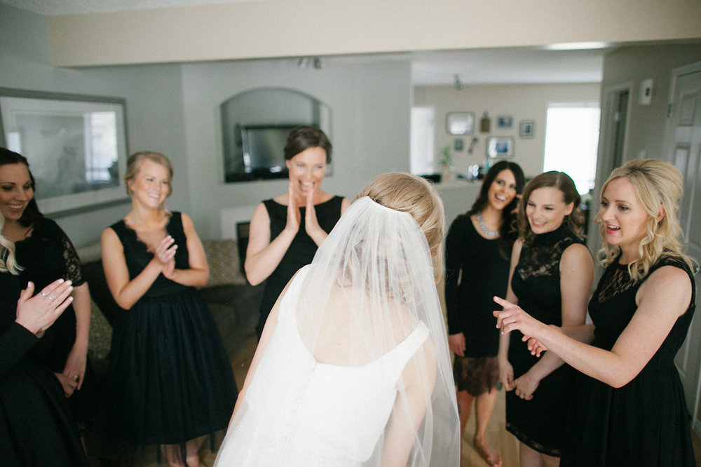 bride and bridesmaids looking at dress