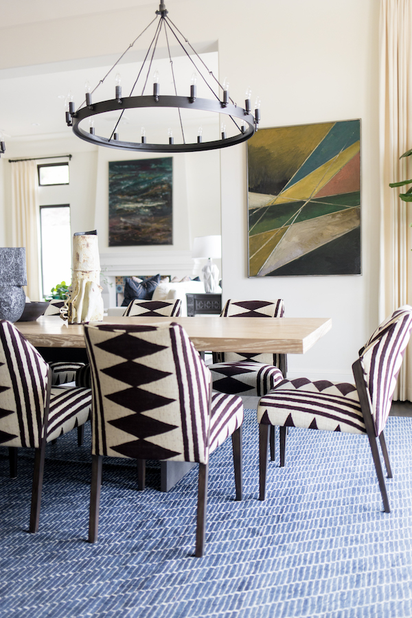 Hilltop Hacienda is an interior design project by Denise Morrison Interiors featuring a dining room with upholstered dining chairs and colorful artwork.