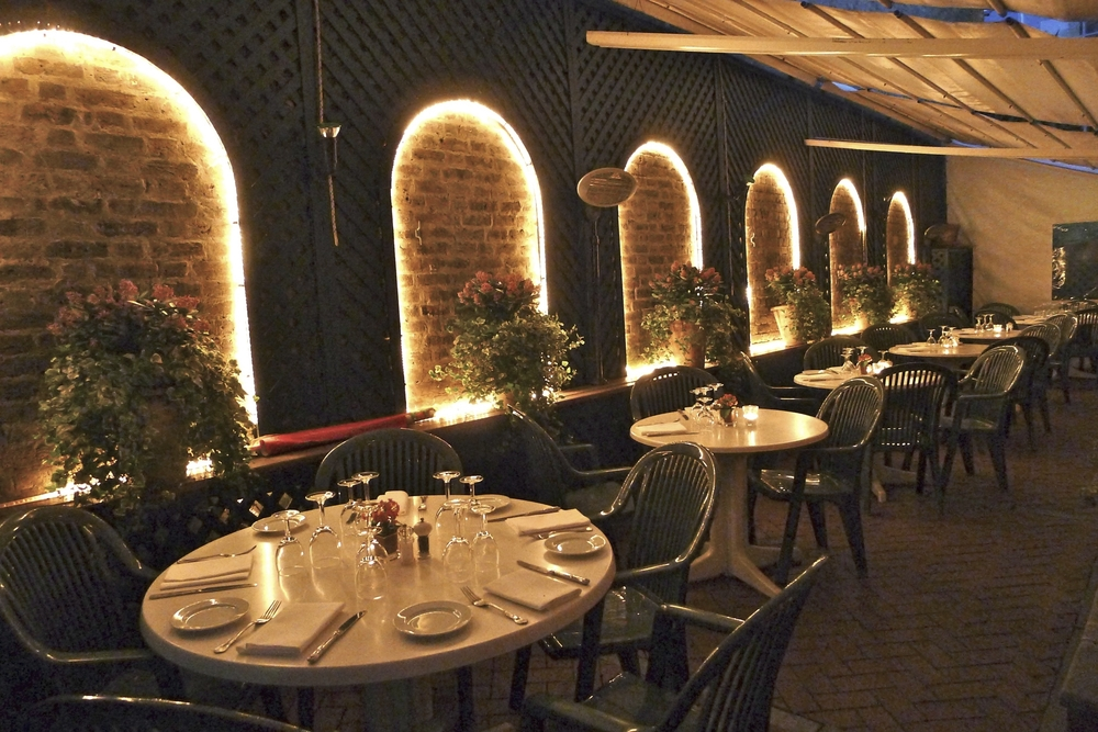 IN THE EVENING, OUTDOOR DINING IS KEPT COMFORTABLE WITH PATIO HEATING AND A RETRACTABLE CANOPY
