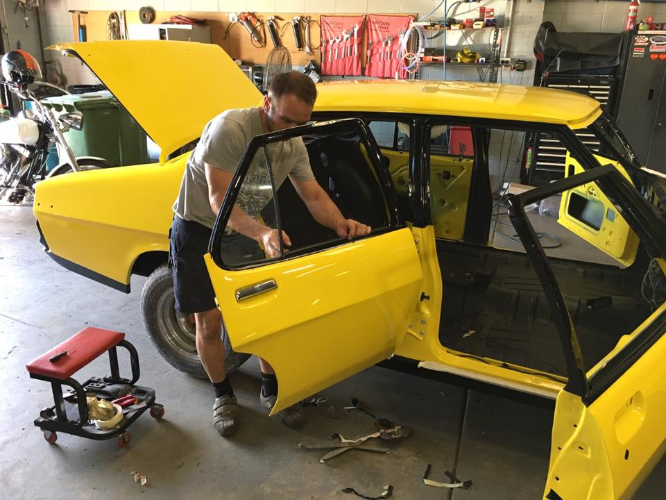 Roland has installed the door mechanisms and side windows. He is now working on mounting the stainless steel window trims.