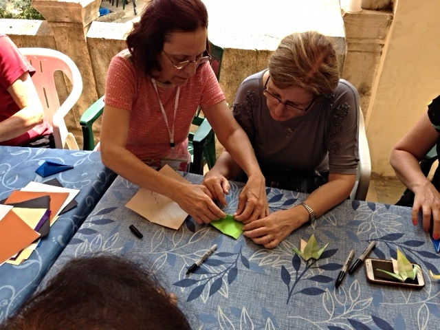 Maahsen, on the left, helps another woman learn the art of origami cranes. Maahsen is from Hasakeh, and she is a good teacher!