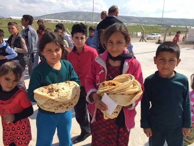 Yazidi IDP children in Iraq, holding bread they were rationed from a new bread bakery, built in the camp to provide food.