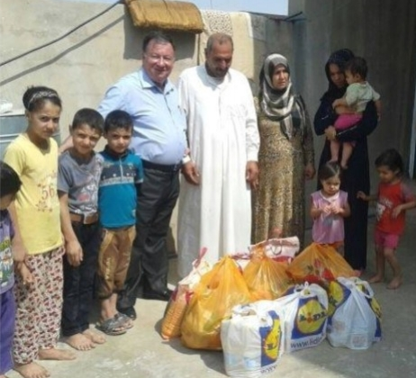 Rev. Haitham of the Presbyterian Church in Kirkuk, Iraq shown delivering food and water to neighbors not from his congregation