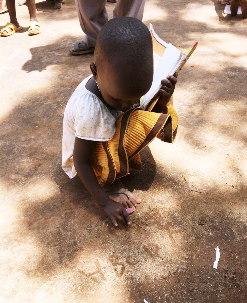 Refugee Nyadoang proudly writes her ABCs in the dirt of the Gambella refugee camp.