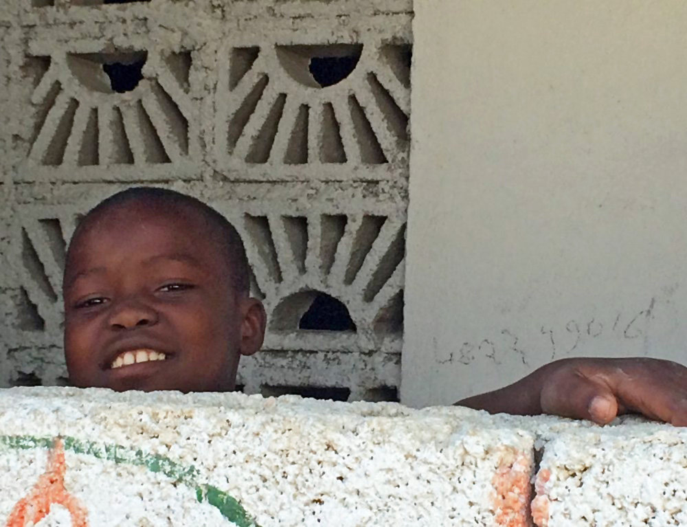 A+young+Haitian+boy,+curious+at+the+commotion,+peers+over+from+the+security+of+the+wall+surrounding+his+house.jpg