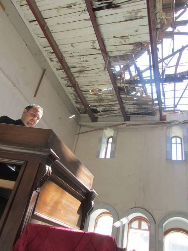 "Rev. Karajilli preaching in the Homs Presbyterian Church after the church received ""collateral damage"" from nearby rocket and mortar fire. The roof has since been repaired and the congregation worships there regularly."