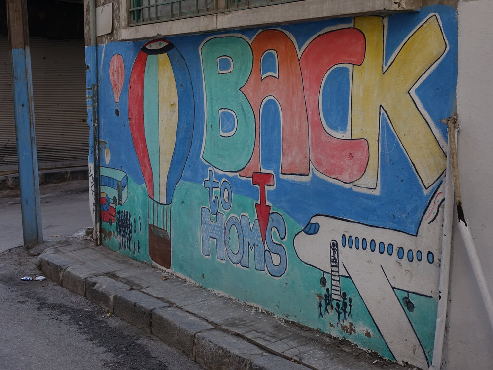 Colorful graffiti on a remnant wall in the city of Homs expressing hope.