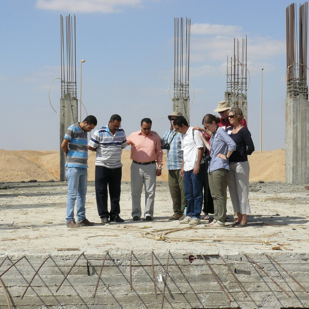 Outreach trip participants praying for soon-to-be pastor Medhat at the site of his new church at El Sadat City.