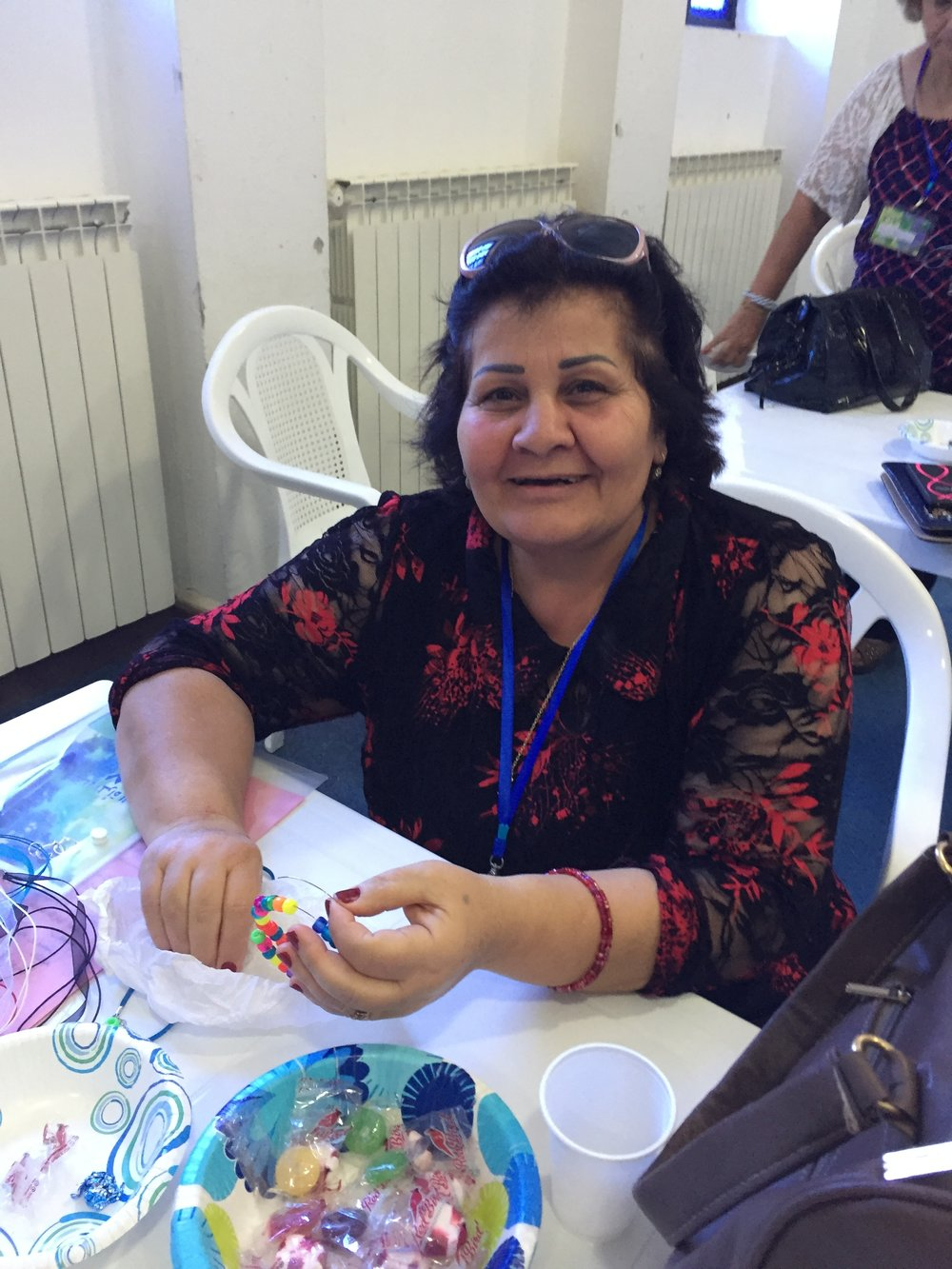A happy bead maker shows her bracelet off.