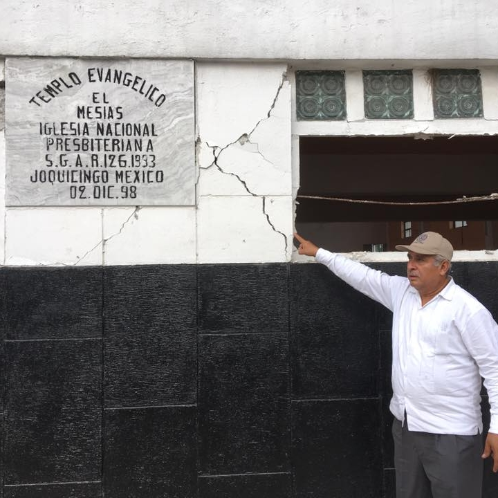 Rev. Hernández showing damage to the structure of Messiah Presbyterian Church in Joquicingo.