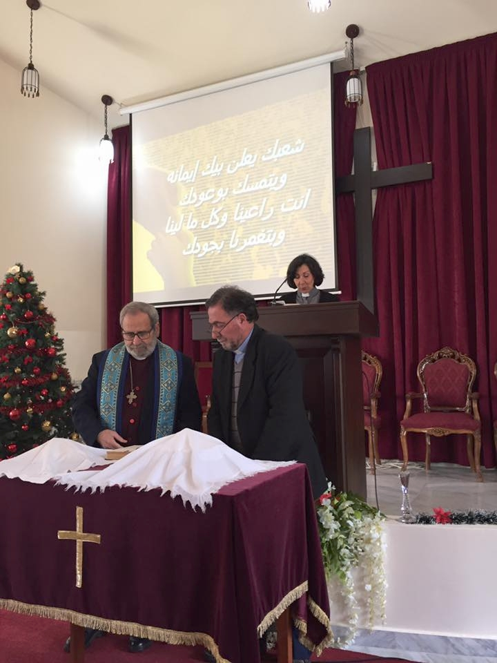 Nuhad Tomeh and Rev. Tony Abboud prepare the elements while Lisa reads the words of institution