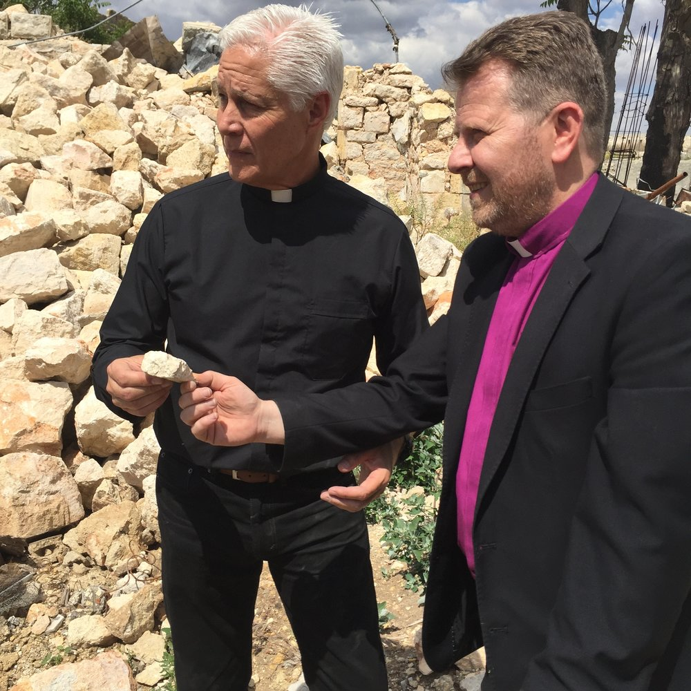 Rev. Jim Wood receives a piece of the ruins of the old Aleppo church from Rev. Ibrahim Nseir