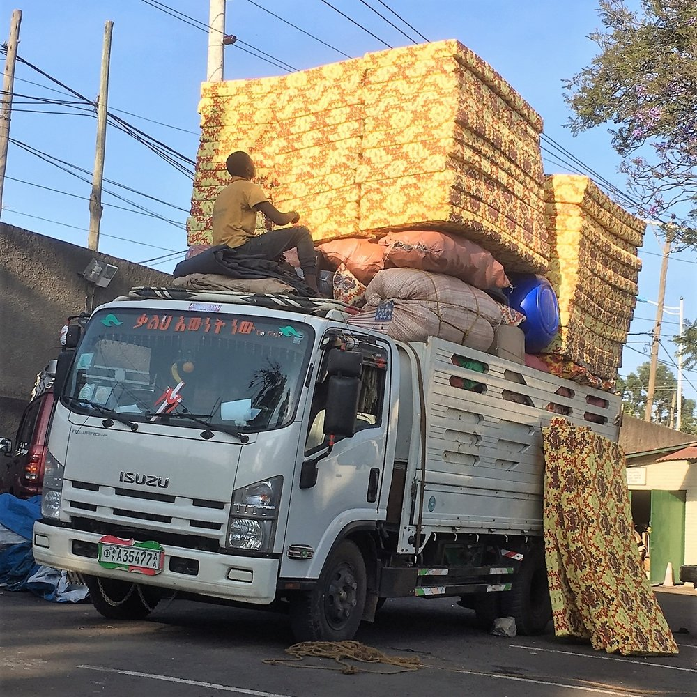 A lorry being loaded with new mattresses for the dormitory at Dembi Dollo-Bethel Evangelical Secondary School