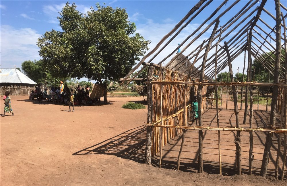 A new classroom being constructed that will be covered with plastic sheeting and thatch to make it 'all weather'. Meanwhile class continues under the tree.