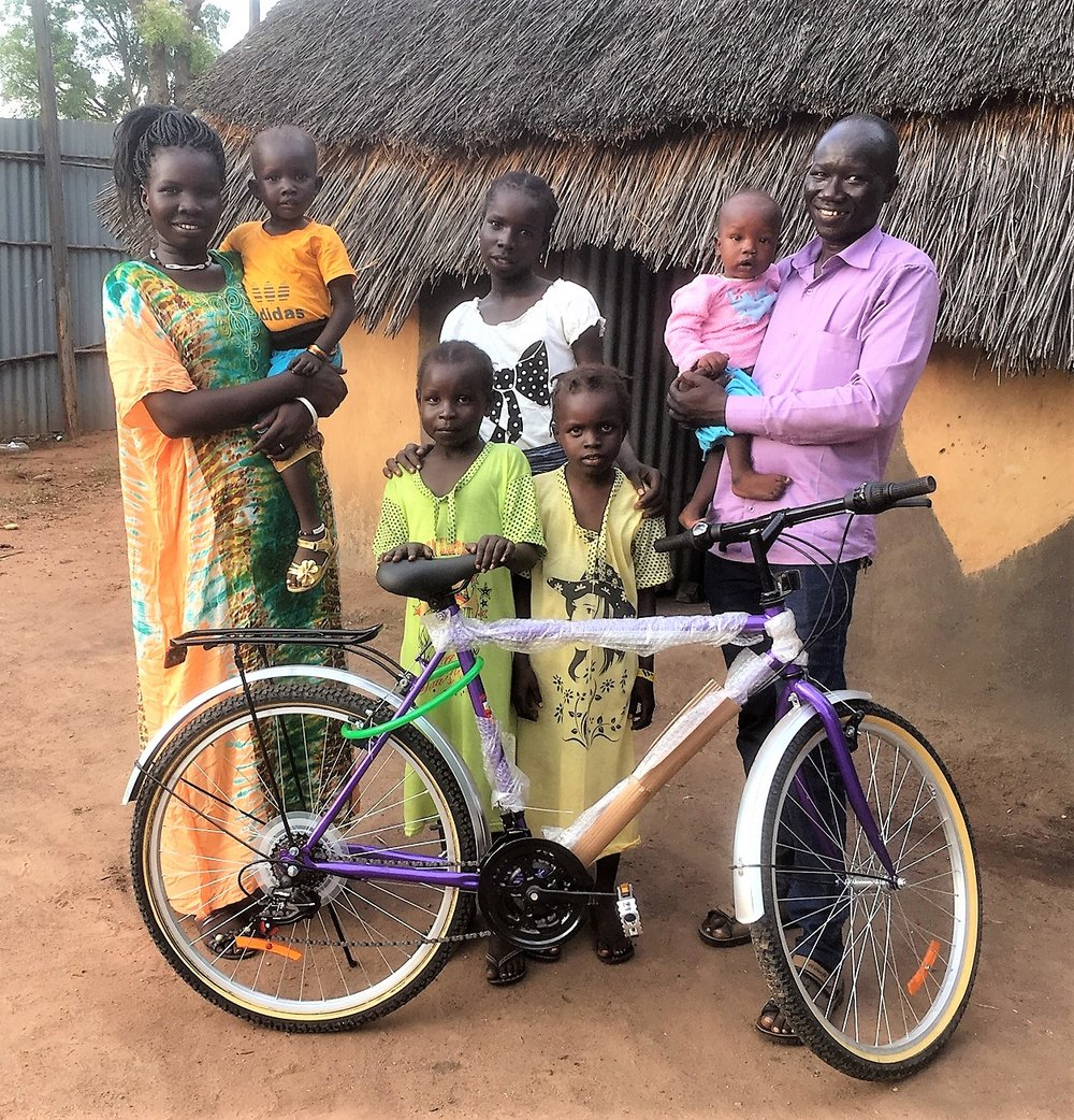 John Jock Gatwech family at their home and new Outreach-purchased Bike for his coordination work in the camps