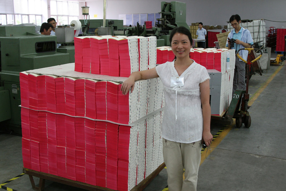 Rev. Fan Jing Fang, one of our Chinese leaders from Jiangsu Seminary, beside a stack of Bibles at the Amity Printing Press when the 2009 English Exchange participants toured Amity Press