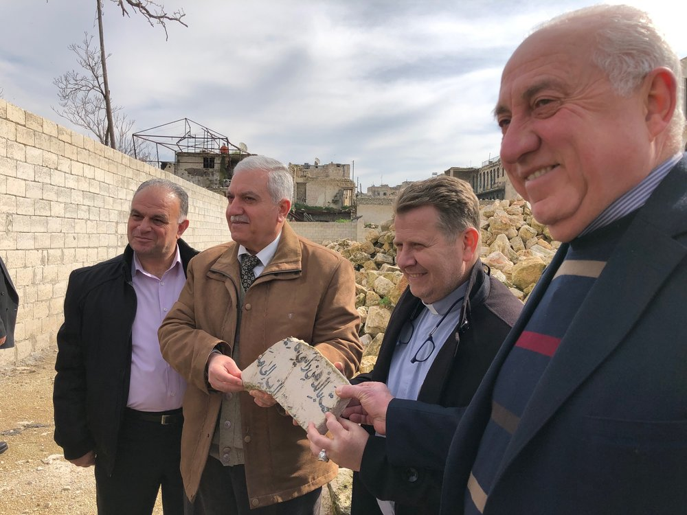 Elder Milad, Elder Feras, Rev. Nseir and Elder Emad holding a piece of the Psalm 23 plaque which used to hang behind the pulpit. It was pulled out of the rubble today and presented to the Outreach team.