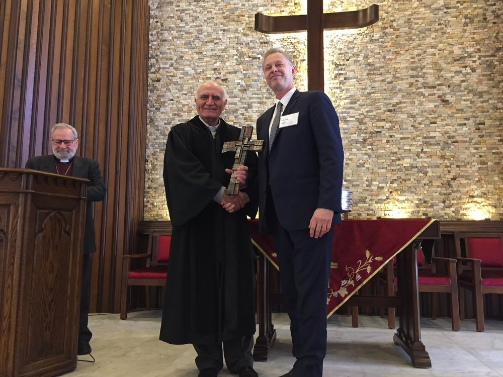 Ted Kulik presents the gift of a cross to Homs church pastor Rev. Yousef Jabbour