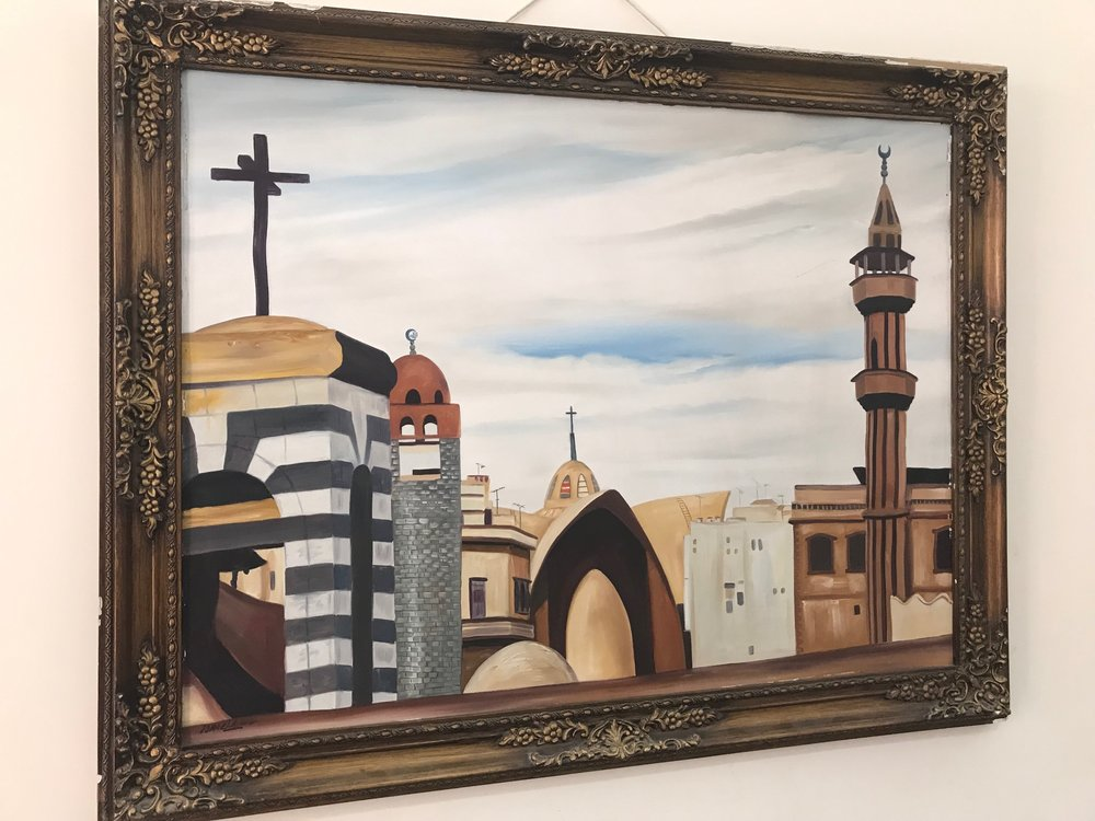 Painting in the Homs church fellowship hall showing the Presbyterian church bell tower, Greek Catholic church, and two mosques