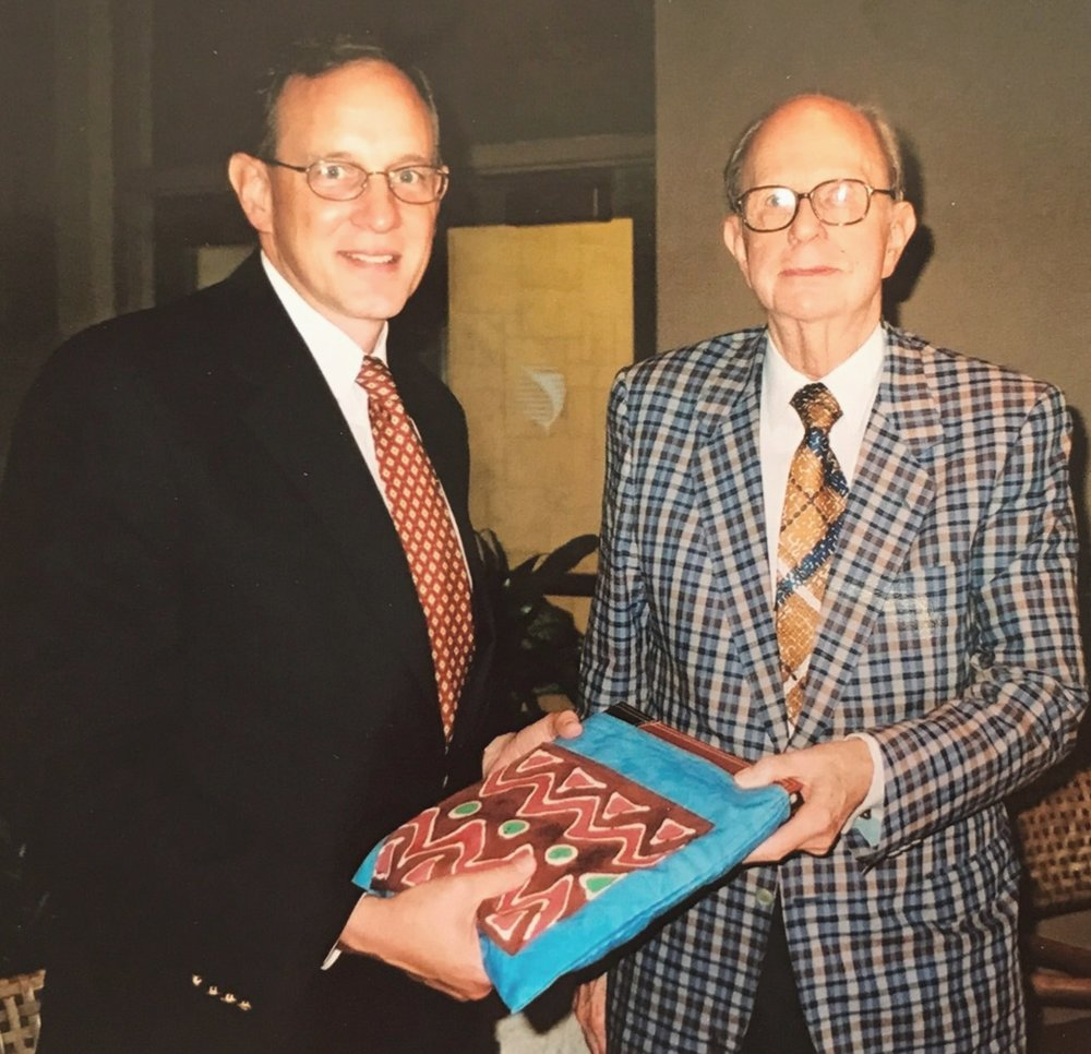 Executive Director Rob Weingartner giving Dr. Alex Booth a gift on his 80th birthday