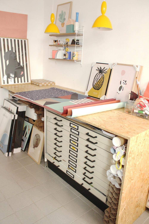 Det høje pakke/krea bord med plads til arkivskab og masser af rammer og plakatrør neden under. Lamperne er fra Muuto.