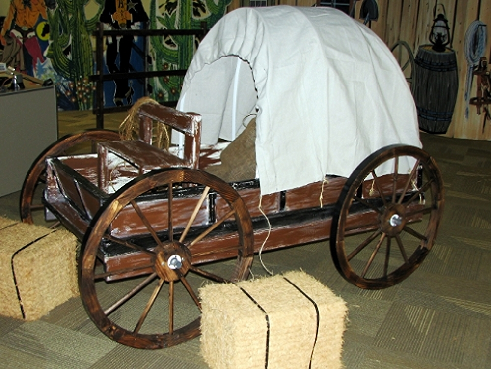 Covered Wagon:  This nice piece measures 3' wide and 6' long. It features a covered roof, a small bench for 2 children, authentic wheels