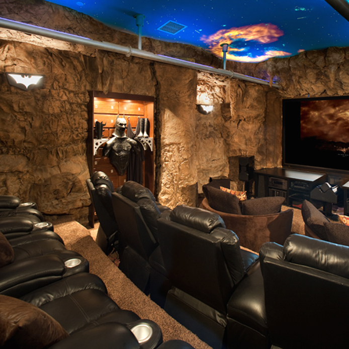 BATMAN CAVE   Home Theater With Exposed Metal Pipes, Display Cases, Batman Sconces & Railing
