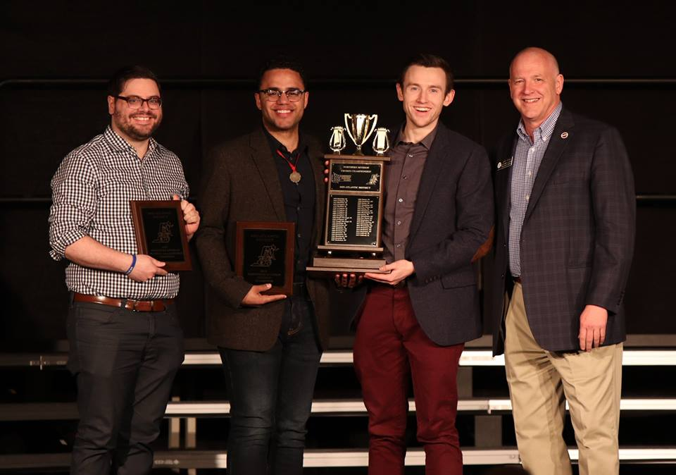 Voices leadership accepting Northern Division Chorus Championship trophy  From L-to-R: Braden Lynk (President), Nick Gordon (Interim Director), BJ Hillinck (Interim Direct), and Gary Plaag (M-AD VP of Contest and Judging)
