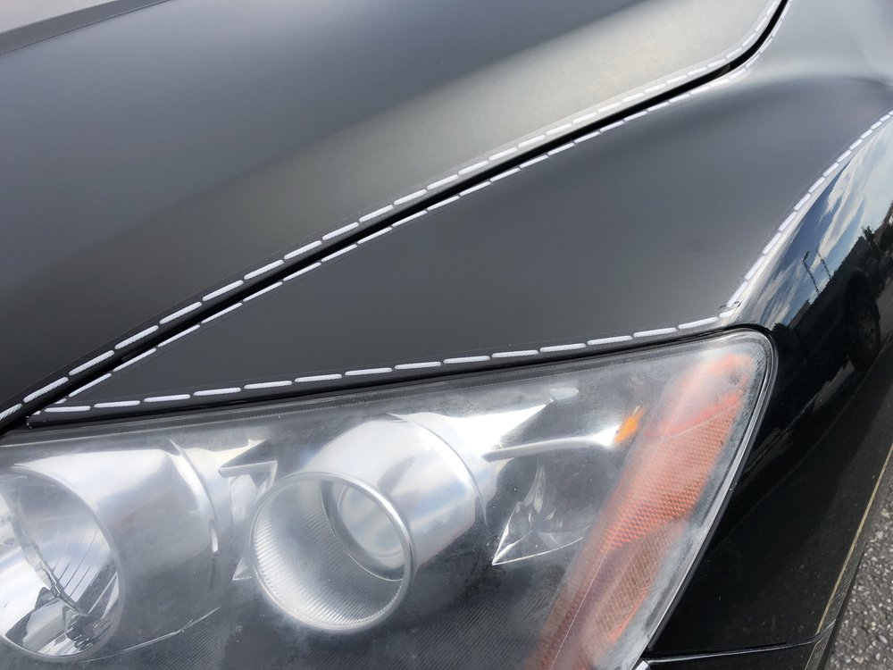 White Stitches on a Black Background Vehicle Wrap