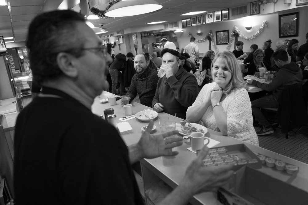 Customers (from left) Brooks Allen with Dale and Mary Pat GoodCourage speaking with owner Ioannis Argenas behind the counter at Evergreen Diner, a diner near Times Square that will close on New Years Eve after more than 24 years in business at the same location.