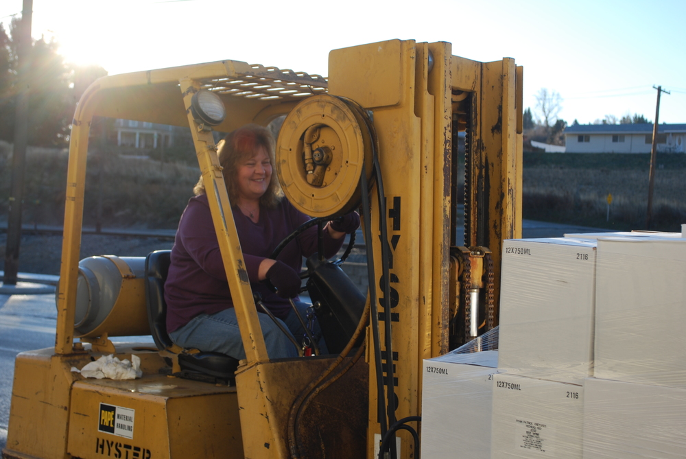 Manager Jayne Stephenson transports wine with the fork lift from the storage room to prep for delivery.