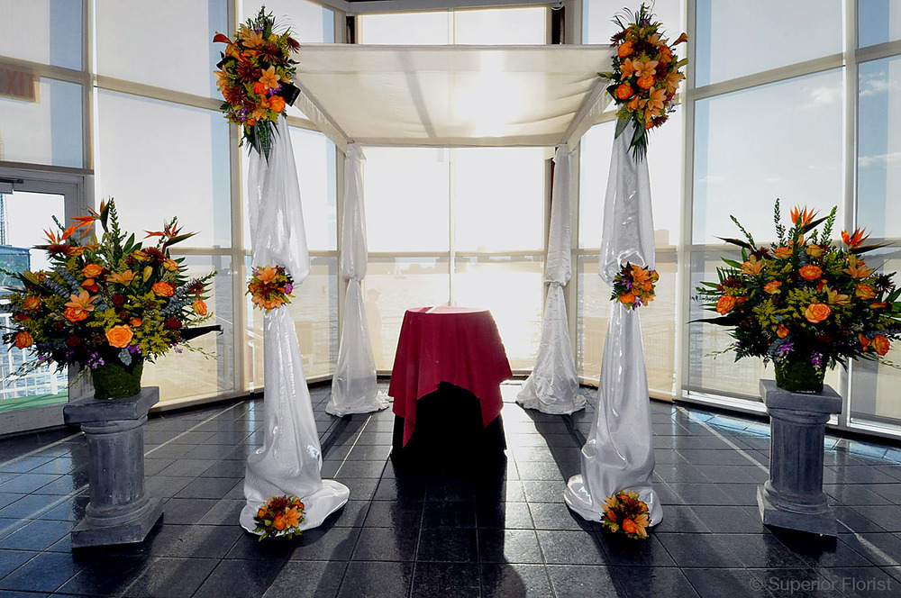 Superior Florist – Wedding Ceremony: Chuppah draped in white, satin fabric. Autumn colored florals. Teardrops and clusters on poles. Flanked by two matching floral baskets.