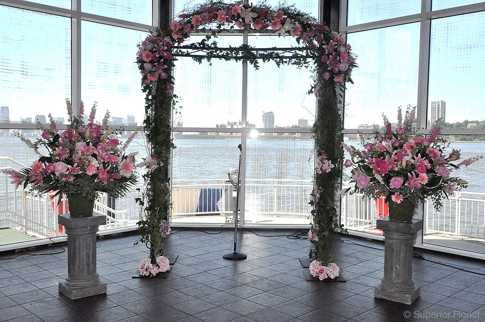 Superior Florist – Wedding Ceremony: Bridal arch with crescent frame attached at top. Flanked by two matching floral arrangements. Flowers in shades of pink.