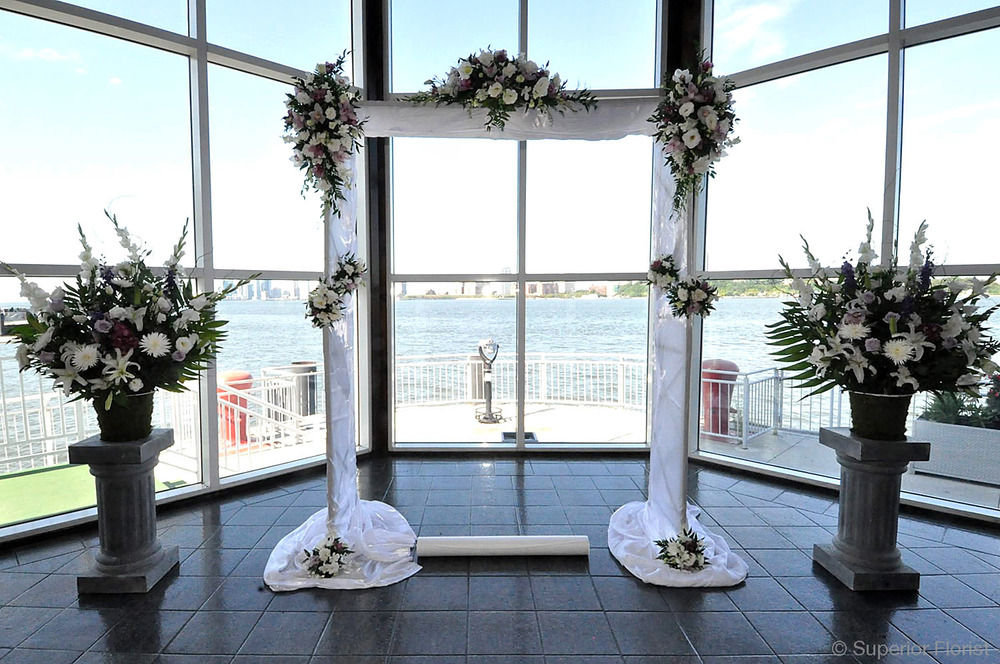 Superior Florist – Wedding Ceremony: Bridal arch draped in white, satin fabric. Teardrops and clusters on poles. Spray arrangement at top center of arch. Flanked by two matching floral baskets.