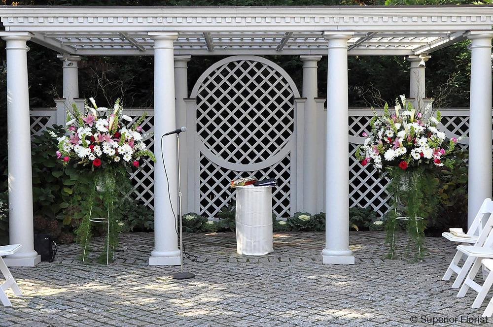 Superior Florist – Wedding Ceremony: Spring wedding ceremony outdoors. Matching floral baskets under gazebo at the New York Botanical Garden.