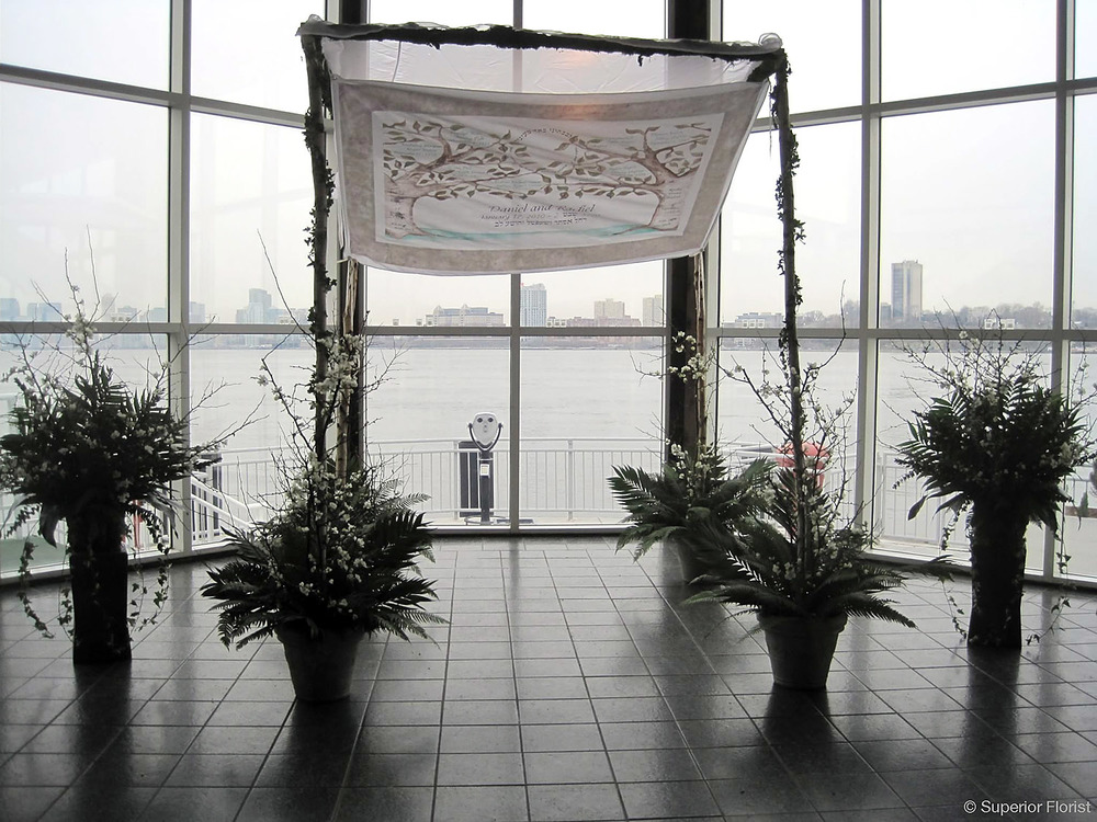 Superior Florist – Wedding Ceremony: Birch pole chuppah with family's custom-made chuppah top. Winter wedding. Light garland of ivy on poles, bases of open quince and foliage. Flanked by two matching arrangements on pedestals.
