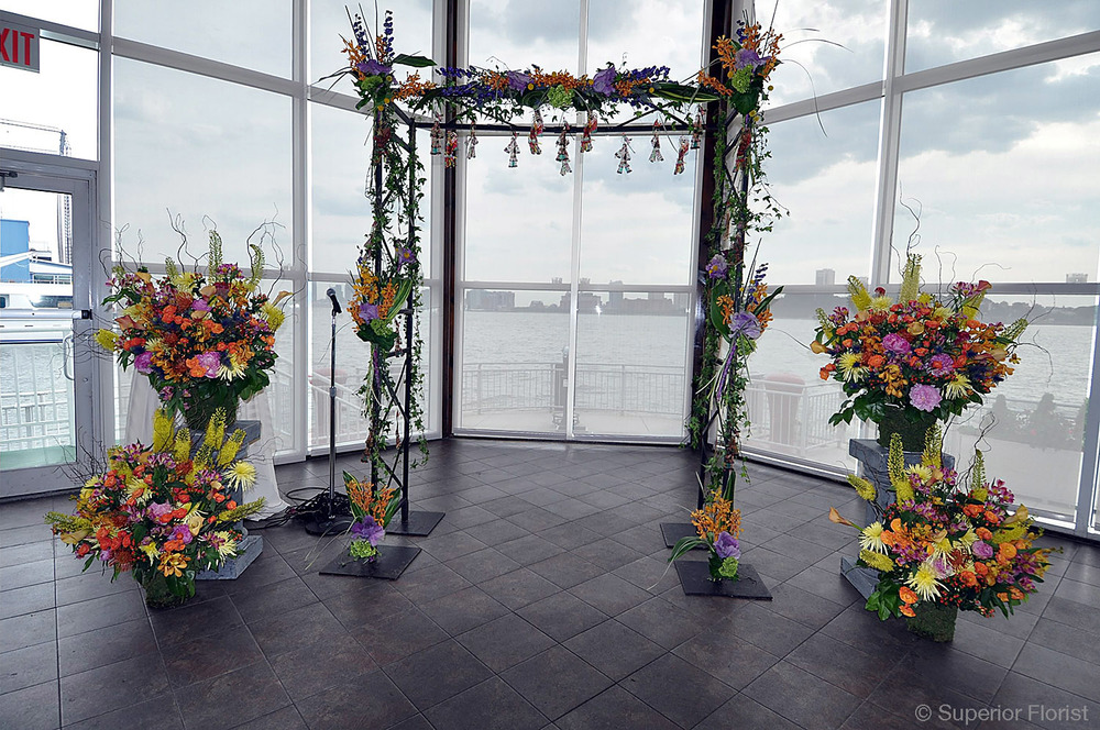 Superior Florist – Wedding Ceremony: Bridal arch adorned with brightly colored, exotic flowers. Arch flanked by four matching basket arrangements.