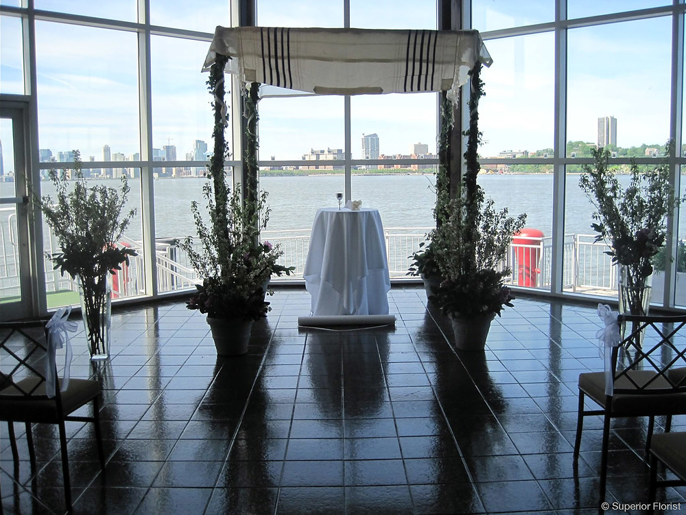Superior Florist – Wedding Ceremony: Birch pole chuppah with family tallis on top. Open cherry branches at bases. Flanked by two large, clear glass vases with cherry branches.