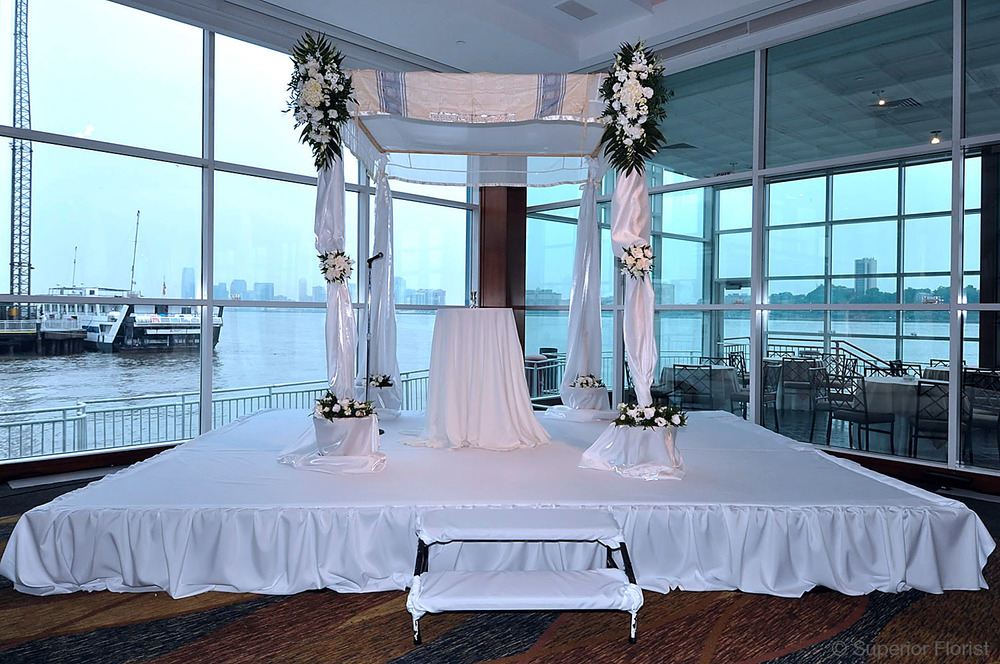 Superior Florist – Wedding Ceremony: Chuppah adorned with family tallis and white bridal satin fabric. Teardrops and clusters of white flowers. Riser draped in white fabric. Pier 60 at Chelsea Piers, NYC.