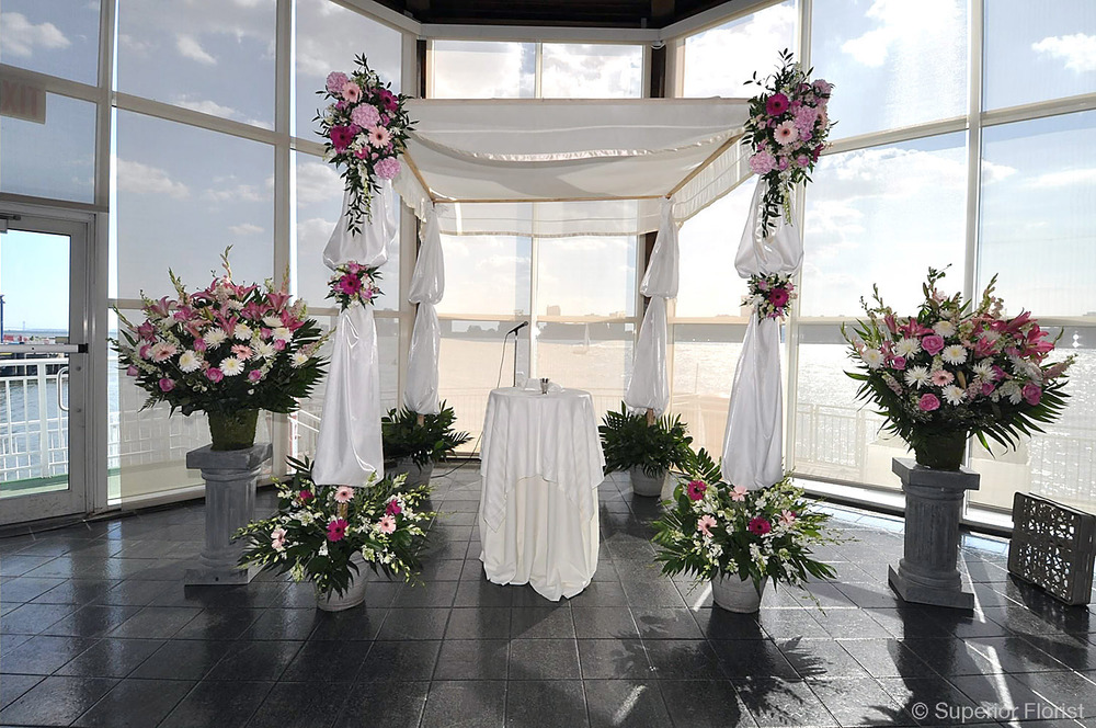 Superior Florist – Wedding Ceremony: Chuppah draped with white bridal satin fabric. Teardrops and clusters of flowers in pink and white. Flanked by two large baskets of floral arrangements on pedestals.