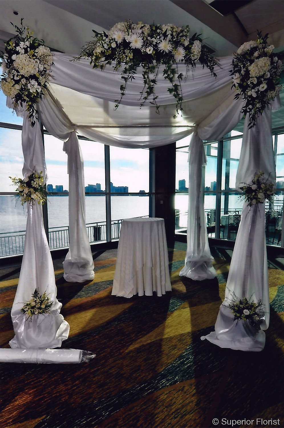 Superior Florist – Wedding Ceremony: Chuppah draped in white, bridal satin fabric. Beautiful arrangements of flowers in all white. Teardrops, clusters and swag arrangements.