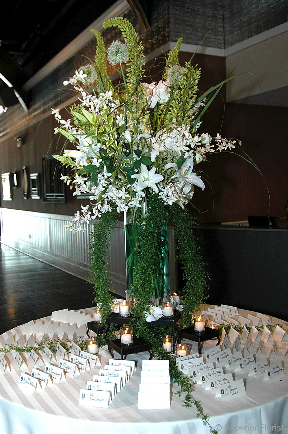 Superior Florist – Weddings – Escort Tables: Eremuras, Casablanca Lilies, white Dendrobiums, and trailing Smilax in a large glass cylinder vase with river rocks in base.