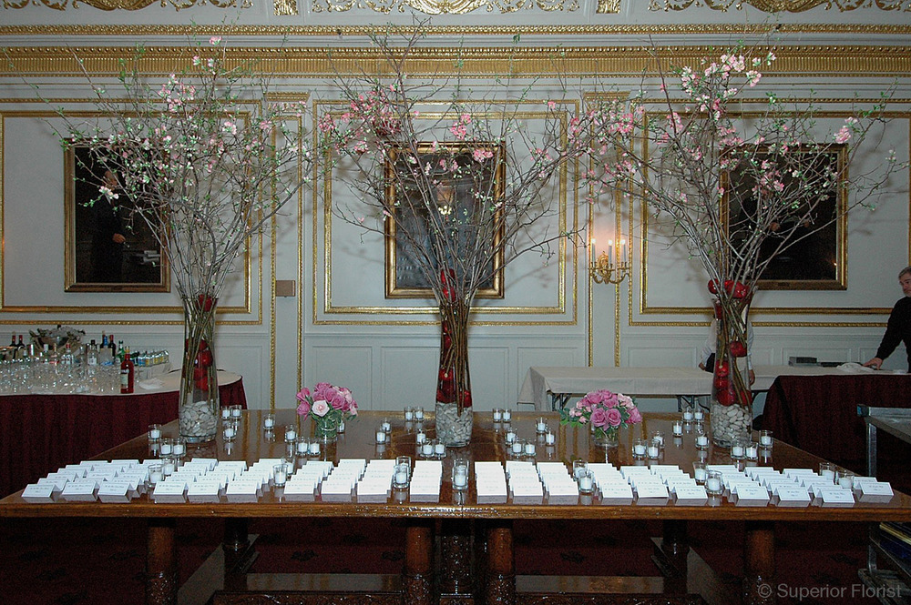 Superior Florist – Weddings – Escort Tables: Open quince branches and submerged red roses in three tall, fluted, clear, glass vases with river rocks in bases. Metropolitan Club, NYC.