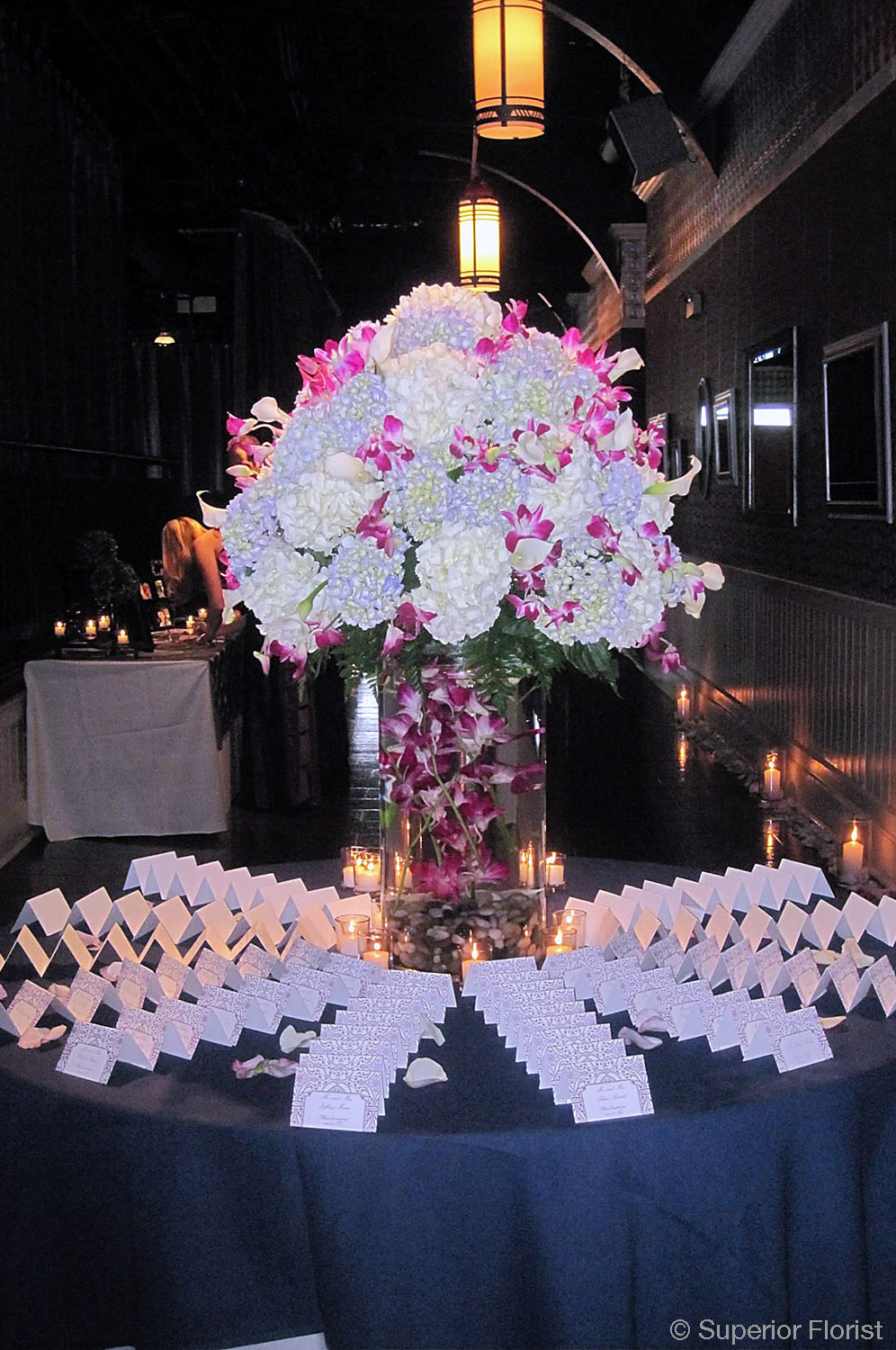 Superior Florist – Weddings – Escort Tables: White and light blue Hydrangeas dotted with Dendrobiums orchids in cylinder glass vase. Variegated Dendrobium orchids submerged in vase with 