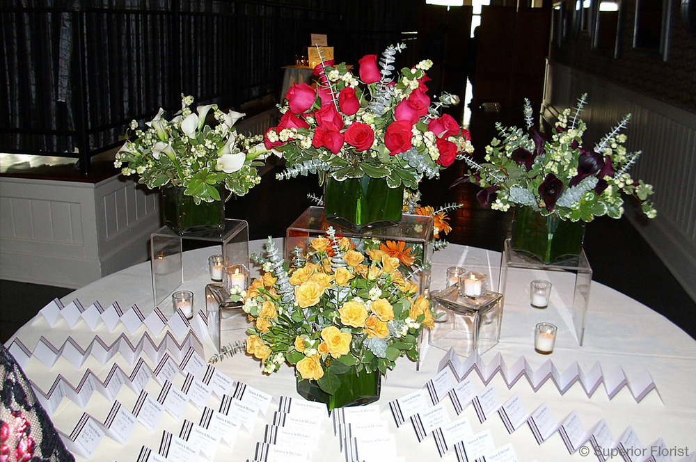 Superior Florist – Weddings – Escort Tables: Roses and Callas balanced out with greenery in a series of glass cubes lined with green wrap.