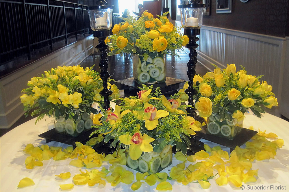 Superior Florist – Weddings – Escort Tables: Bouquets of Freesias, Ranunculus, Cymbidiums and roses. Submerged lemon slices in glass vases. Scattered yellow rose petals on table.