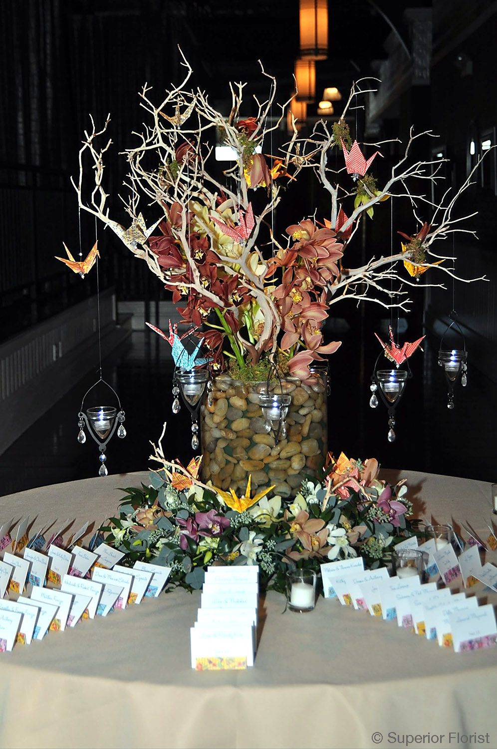 Superior Florist – Weddings – Escort Tables: Manzanita branches; miniature Cymbidiums and hanging votive candles. Origami cranes made by the bride. Matching ring of flowers at base. Clear, glass vase filled with river rocks.