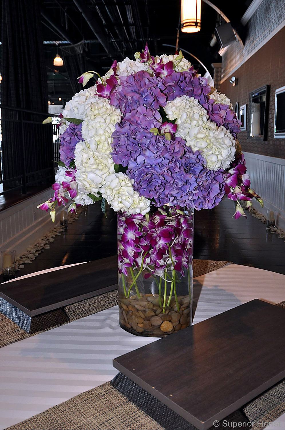 Superior Florist – Weddings – Escort Tables: Large bouquet of purple and white with submerged variegated Dendrobiums in a clear, glass cylinder vase with river rocks.