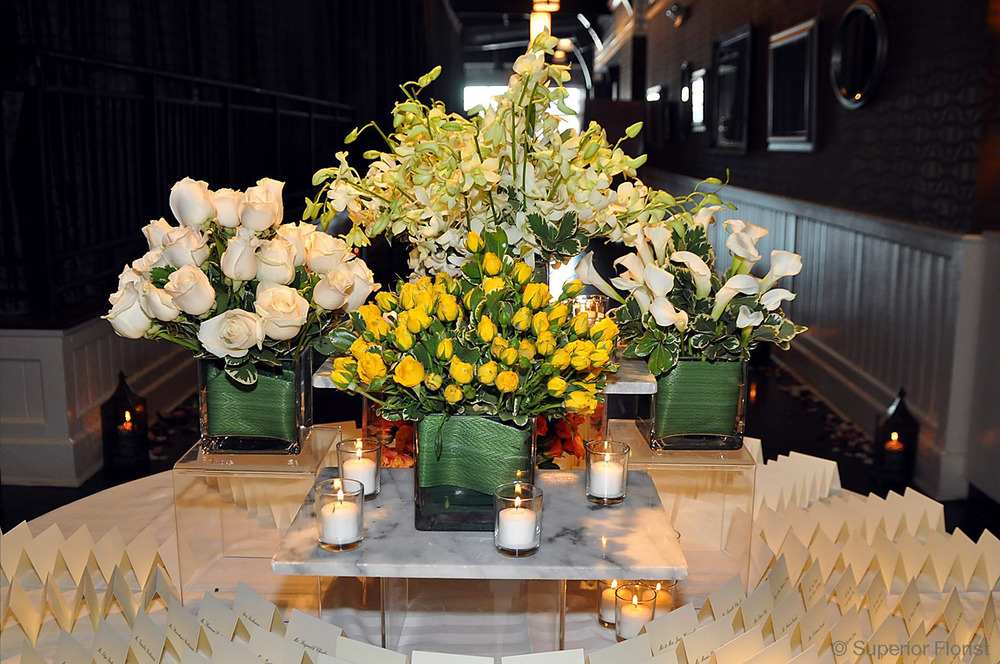 Superior Florist – Weddings – Escort Tables: Bouquet series of roses, orchids and Callas in clear, glass cube vases.